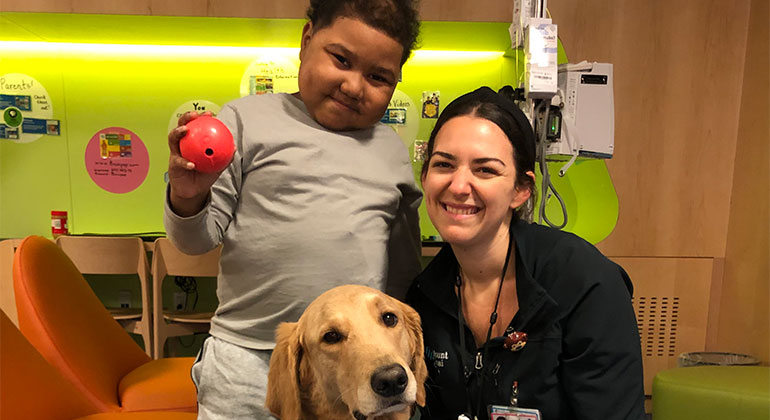 Image of little boy and nurse with dog