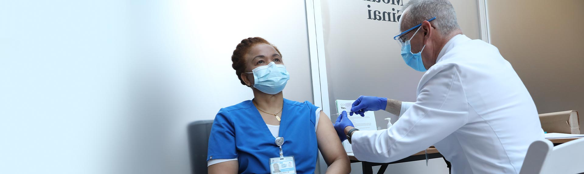 Image of doctor putting vaccine on nurse