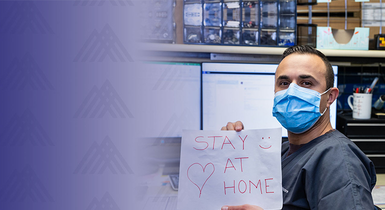 Nurse holding a stay at home sign