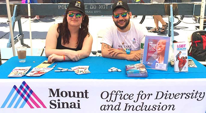 "A man and woman sit behind a booth with a sign that says ""Mount Sinai Office for Diversity and Inclusion"""