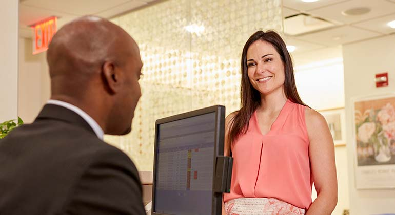 Image of patient in pink talking to front desk staff