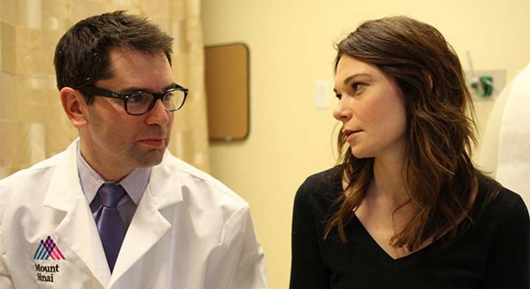 Image of doctor in glasses looking at patient