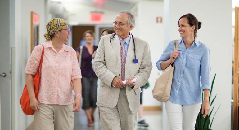Image of Dr. and patient with caregiver walking together