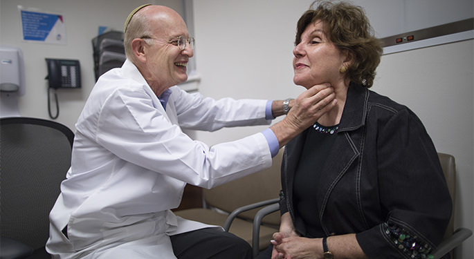 Dr. Terry Davies examines a patient's thyroid