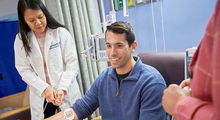 Young man, sitting in chair, receiving infusion