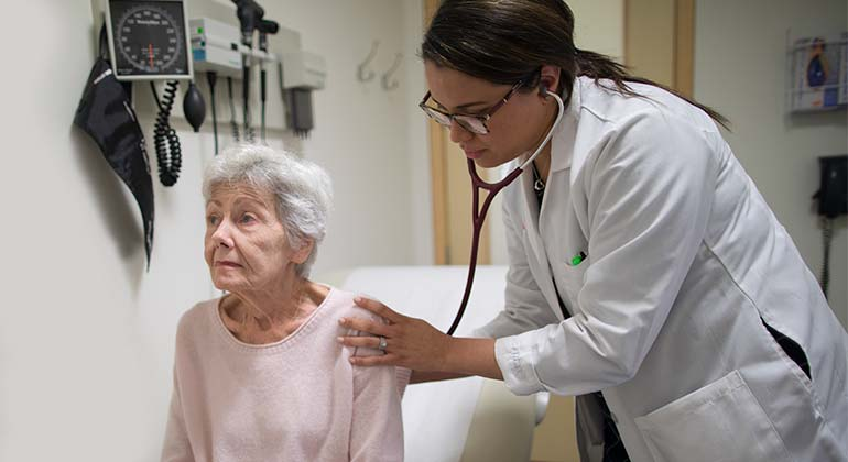 Female doctor using stethoscope on seated female geriatric patient in examination room