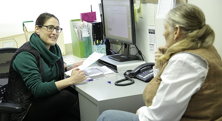Patient speaks with social worker, sitting at desk