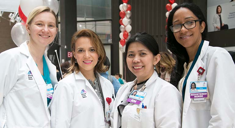 Four female nurses posing at an event. Each are in a lab coat