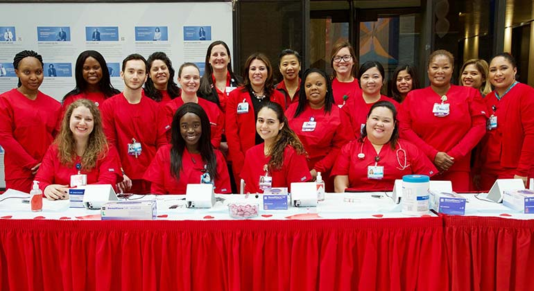Group of nurses sitting and standing around a table at the annual Go Red for Women event at The Mount Sinai Hospital. All are in red scrubs
