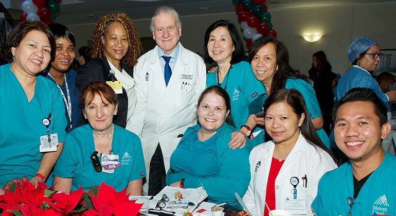 Group of female and male nurses in scrubs posing with male physician