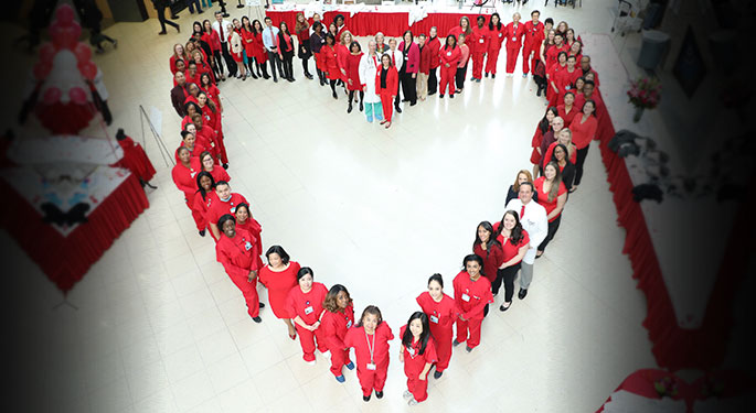 People in red forming a heart