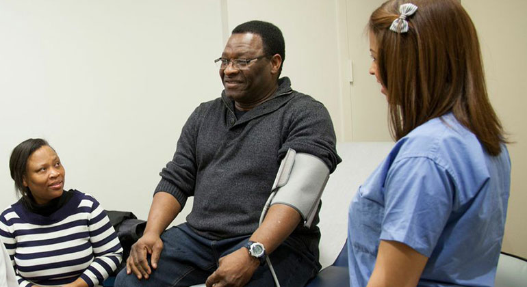 Patient getting his blood pressure taken by a nurse