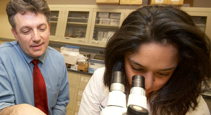 Image of Dr. Samuel Gandy, with student observing through microscope at the Center for Cognitive Health