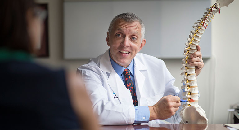 Doctor with model of spine