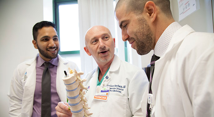 Three male doctors discuss a model of the spine