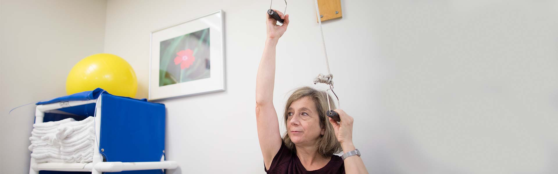 Seated woman works vertical pulleys overhead in exam room