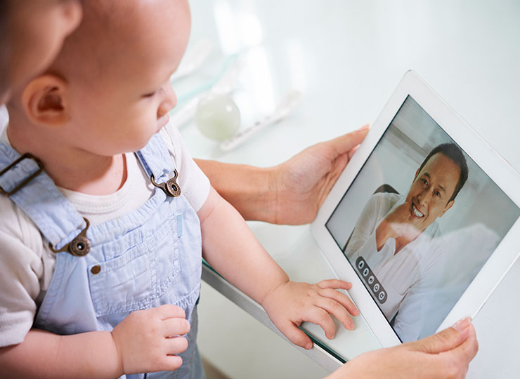 Photo of parent consults with doctor via telemedicine