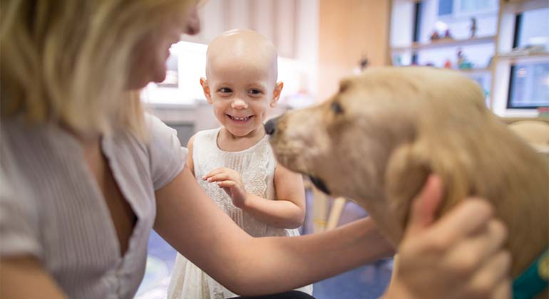Little girl with mom and therapy dog