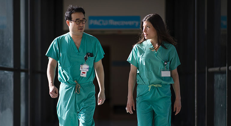 Image of two surgeons walking down the hall