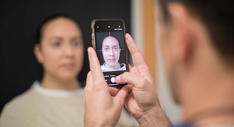 Man taking a picture of woman's face with a phone