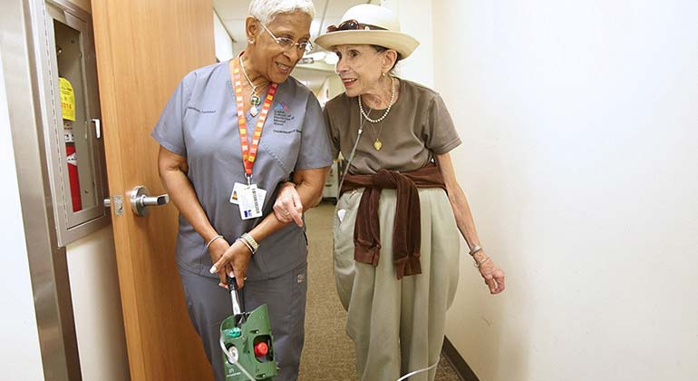 nurse walking with patient in ahll