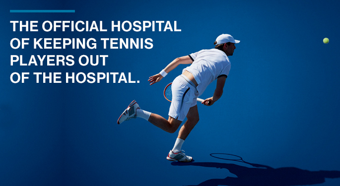 "Image of male tennis player after hitting ball. Text reads ""The official hospital of keeping tennis players out of the hospital."" The US Open logo is in the lower left corner."