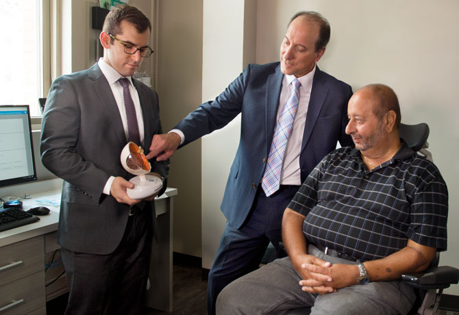 A photo showing Richard Kaplan, MD, a vitreoretinal surgery fellow at NYEE and Ronald Gentile, MD, with patient Joe Mauro explaining the new procedure for eye injections.