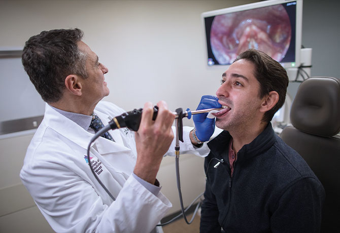 A photo of Mark S. Courey, MD, performing SEES evaluation on patient Julio Bragado-Young at The Grabscheid Voice and Swallowing Center of Mount Sinai.