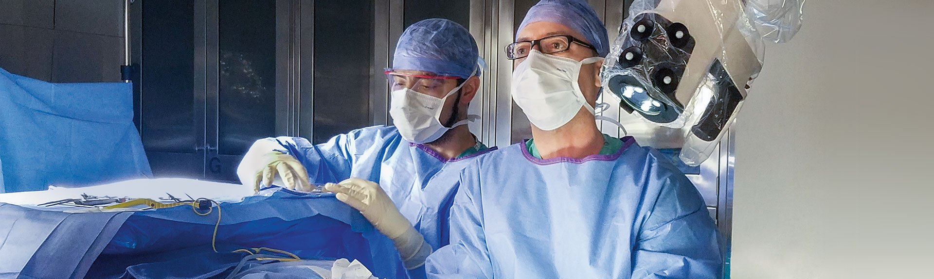 A photo of George Wanna, MD, using exoscopic technology in the operating room.