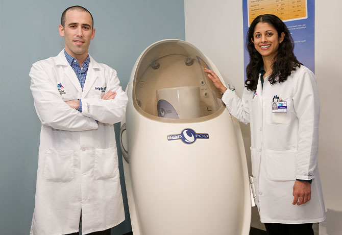 A photo of Reshmi Srinath, MD, and Avigdor Arad, PhD, RDN, CDE, at the Mount Sinai PhysioLab with one of their programs' diagnostic tools, the Bod Pod, which measures the percentage of body fat and lean body mass.