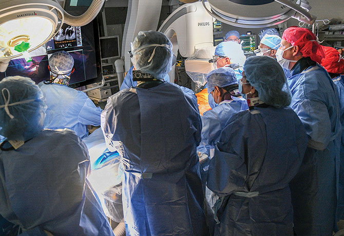 A photo showing David H. Adams, MD, leading a multidisciplinary team performing transcatheter mitral valve replacement.
