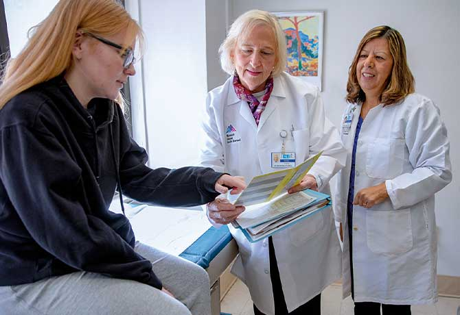 A photo shows Paige Dobbyn with her doctors, Patricia Walker, MD, and Maria Berdella, MD