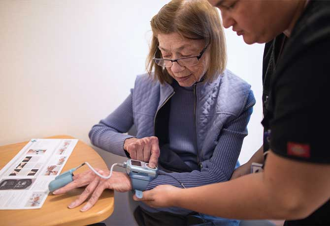 A photo shows Patient Phyllis Weiss receiving a WatchPAT diagnostic device at the Mount Sinai – National Jewish Health Respiratory Institute