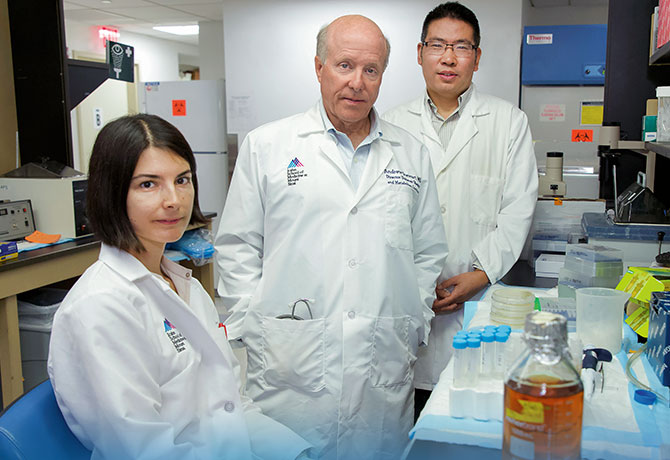 A photo of Andrew F. Stewart, MD, center, with team members Esra Karakose, PhD, and Peng Wang, PhD