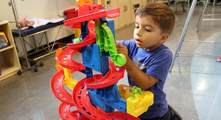 Young male patient plays with toys at the Kravis Children's Hospital