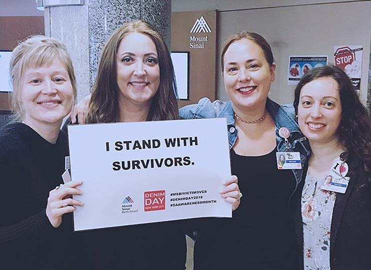 "Social workers holding a sign saying ""I stand with survivors"""