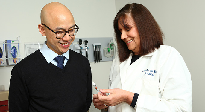 Dr. David Lam and Cynthia Esrig, NP, look at syringe