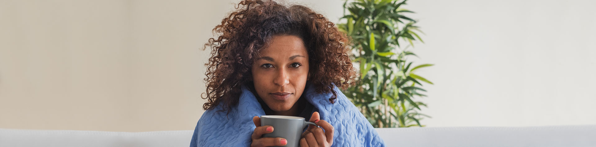 Woman under blanket with mug