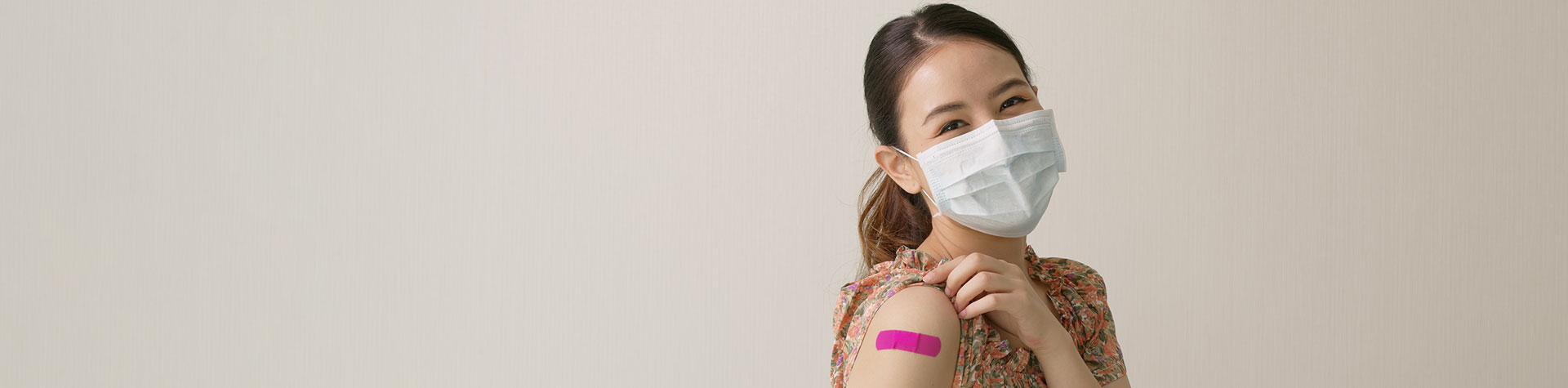 Masked patient with band aid from vaccine shot