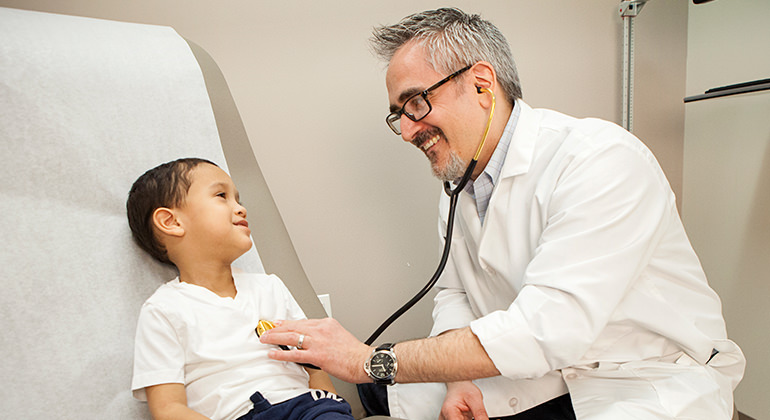 doctor examining child using a stethoscope while on patient bed