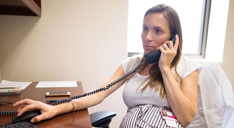 Pregnant woman on telephone at desk
