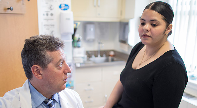 Dr. Steven Weinfeld in discussion with female patient during office visit