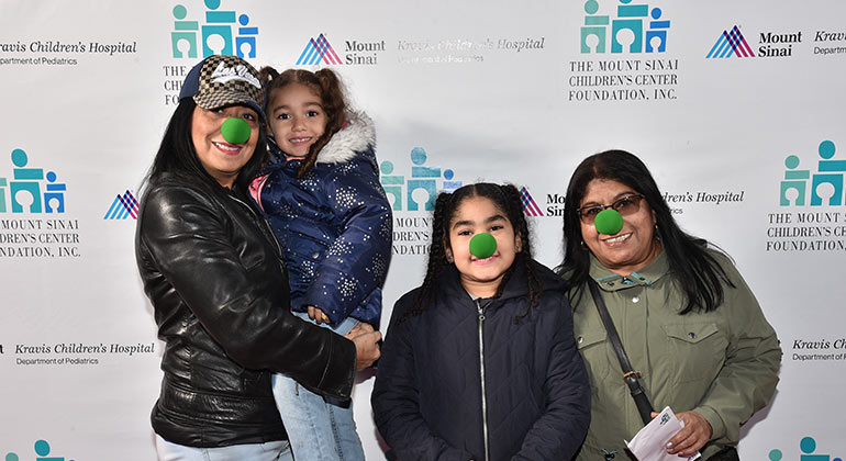 Two women and two girls wearing green clown noses