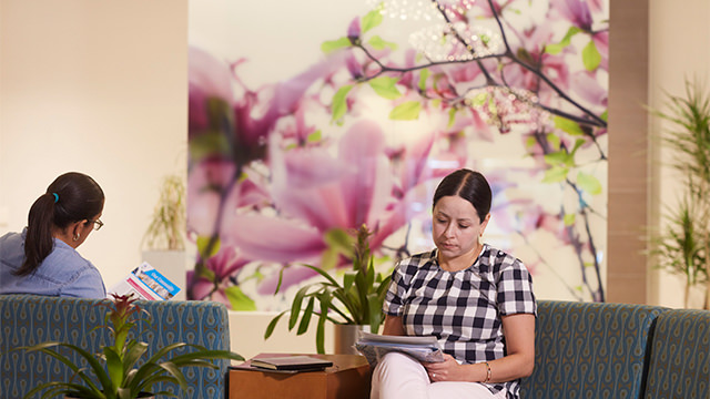 Two women sitting in front of picture of flowers in waiting room