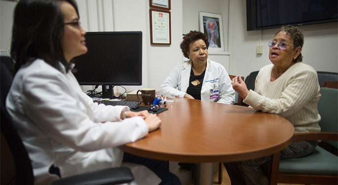 image of Dr. Fifi and faculty in discussion with patient, in an office setting