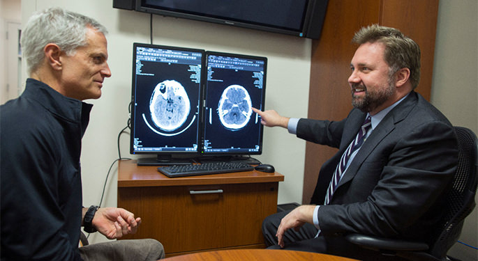 image of Dr. Mocco and patient discussing brain scans on computer screens
