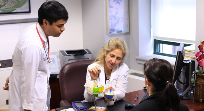 image of Dr. Germano reviewing brain model with another physician and patient in office setting