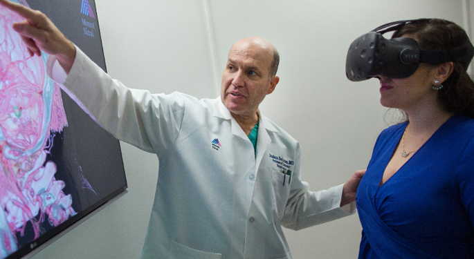 image of Dr. Bederson with staff member using goggles to view brain scan on screen