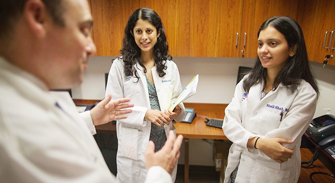 Doctors Tamler, Srinath, and Shah discussing a case in a cabinet-lined space