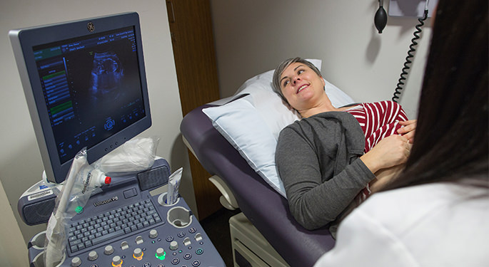 Doctor performing sonogram on pregnant woman